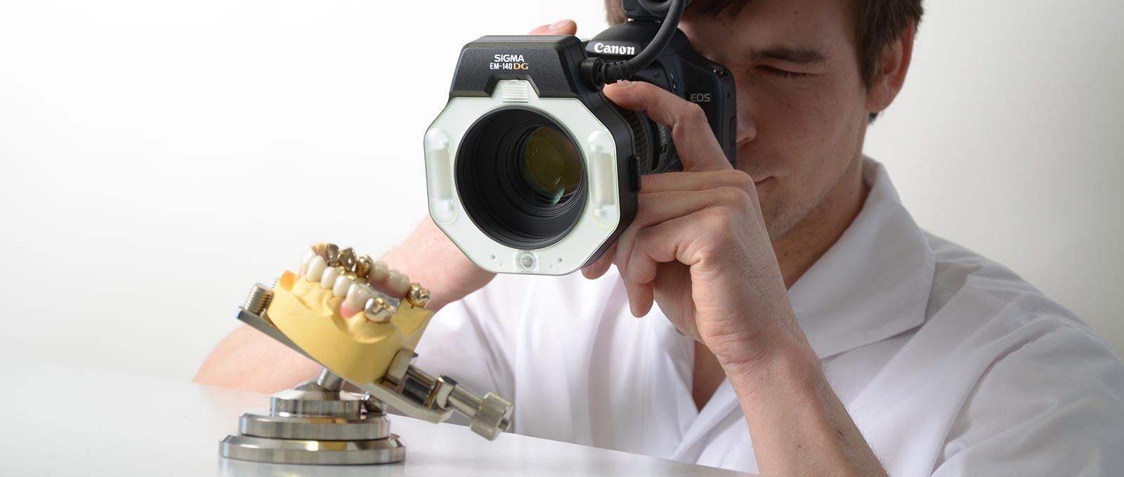 Ein Zahntechniker von Rißmann Zahntechnik fotografiert eine zahntechnische Arbeit.