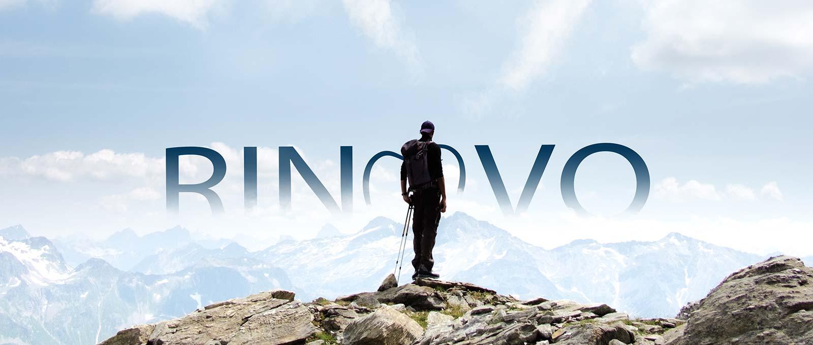 Ein Wanderer steht auf einer Bergspitze und betrachtet die Buchstaben Rinovo von Zahntechnik Rißmann, einem Dentallabor aus Sachsen-Anhalt, über den Gipfeln.